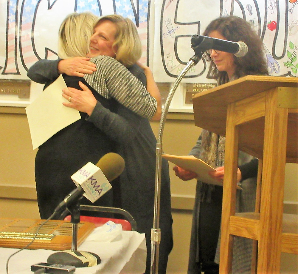 """Teacher of the Year"" Teresa Hughes hugs the Shenandoah Education Association's Cindy Novinger after Hughes' award was announced, and waiting with the presentation of it is the SEA's Tammie Stettler. See more photos below here."