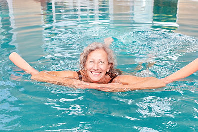 Happy senior woman with swimming aid at
