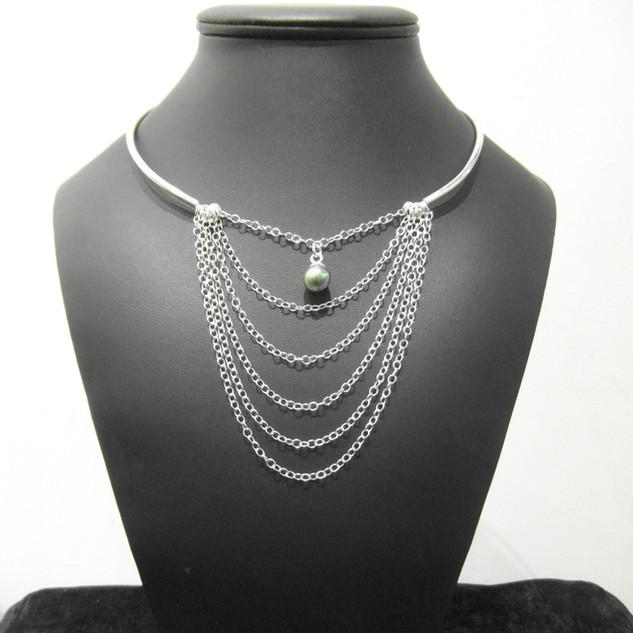 Plusieures chaînettes montées sur un tour de cou rigide, pendentif serti d'une perle de Tahiti