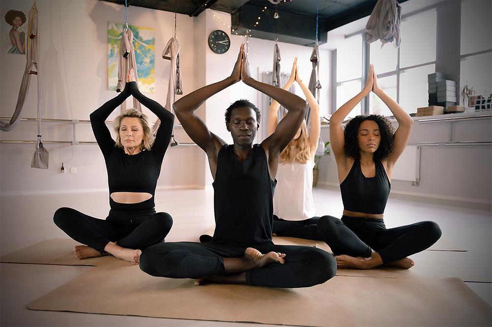 Three women and a man practising yoga