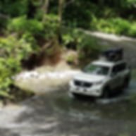 4x4 crossing a river in a tropical forest