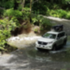 Véhicule tout terrain traversant une rivière dans une forêt tropicale