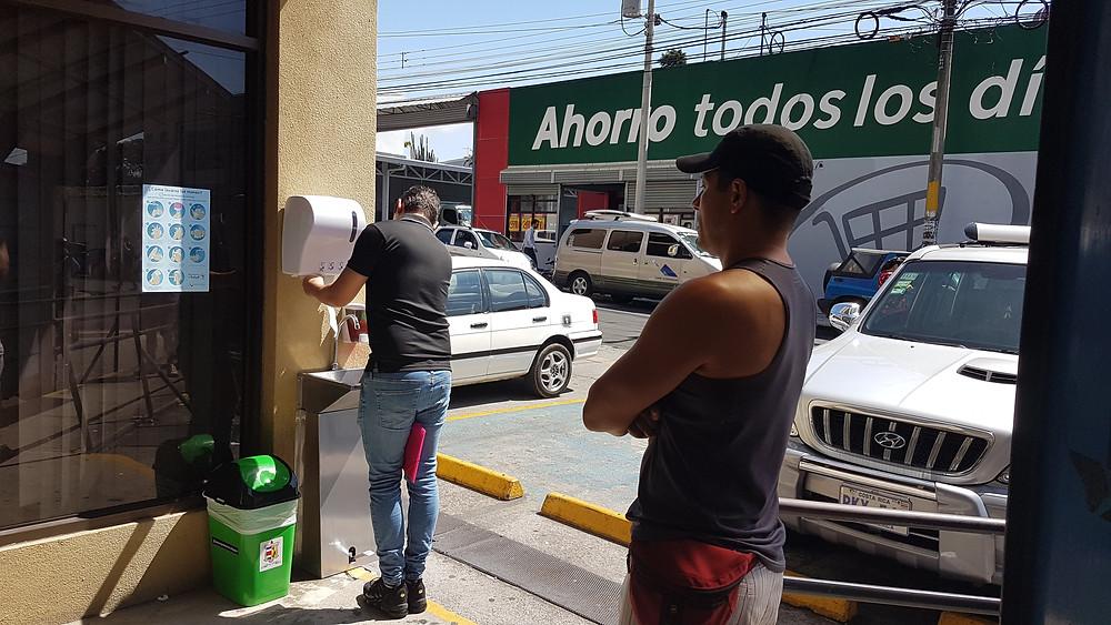 Un usager se lave les mains avant de rentrer dans un lieu public. Un autre attend son tour à distance.