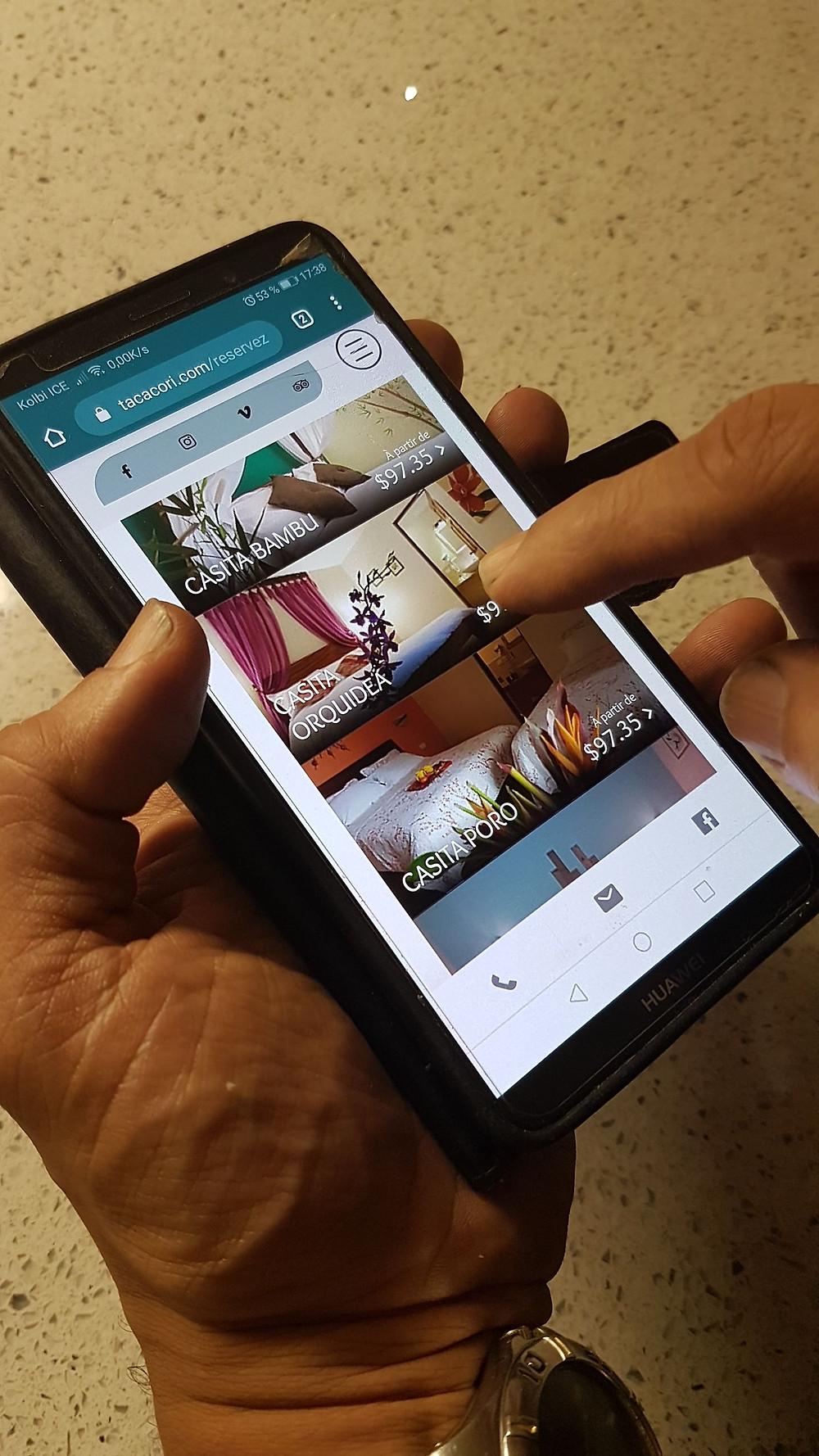 Un téléphone portable affiche une page de réservation sur le site de tacacori ecolodge