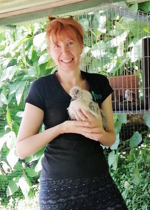 Une femme tient un poulet contre elle