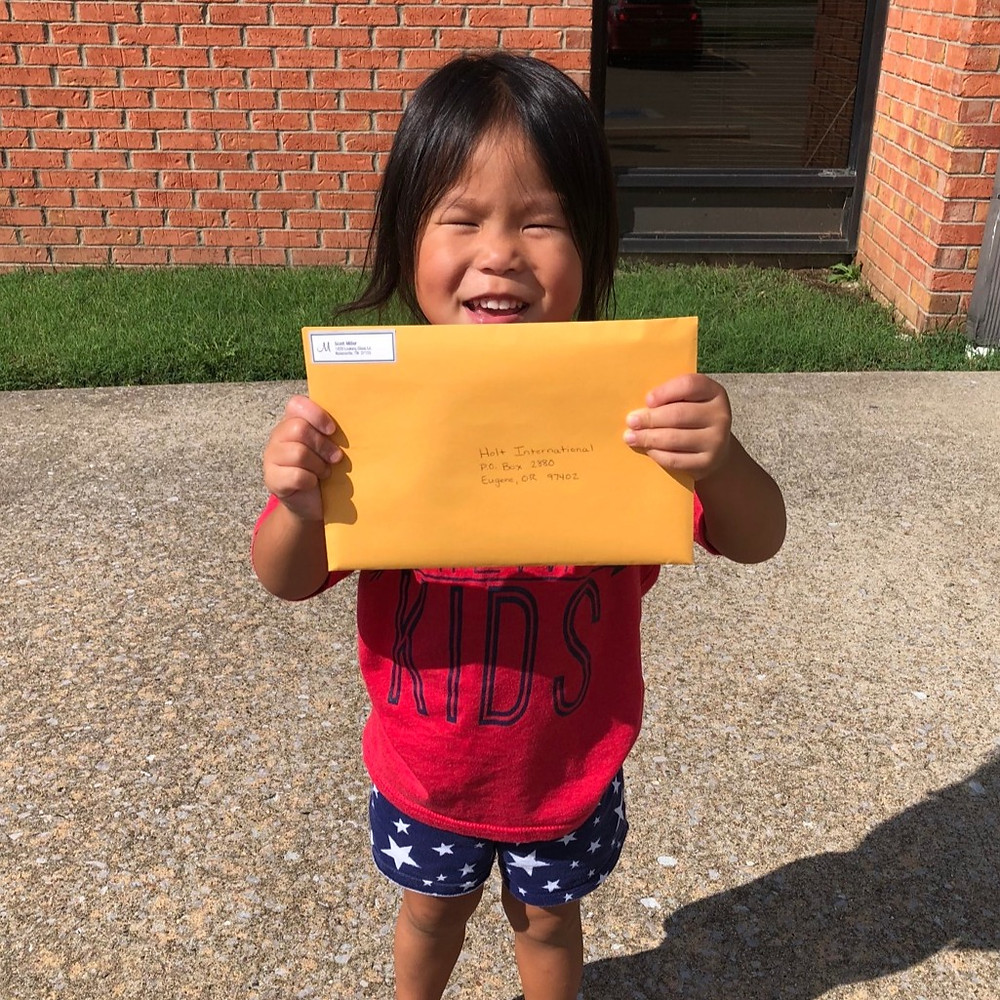 Brielle mailing our adoption adoption to bring her brother home from South Korea!