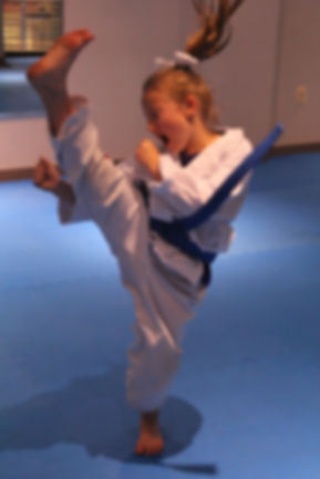 Girl doing a high front kick wearing a martial arts uniform