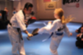 Girl kicking target paddles that an instructor is holdingmartial arts-target kick
