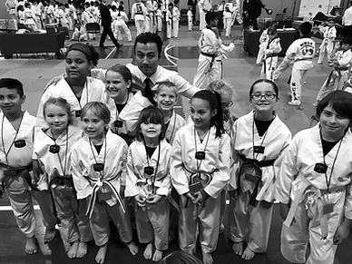 A group of kids smiling at a martial arts competition