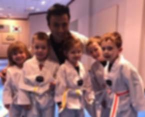 Smiling kids and instructor wearing martial arts uniforms
