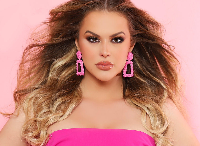 Sierra Sandison headshot, wearing pink earrings and a pink outfit