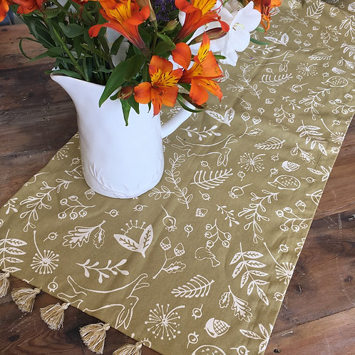 Pretty table runner in a saffron/green colour way with hedgerow design featuring hares and hedgehogs