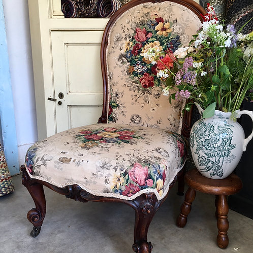 An antique Victorian nursing chair with worn floral fabric at Source for the Goose