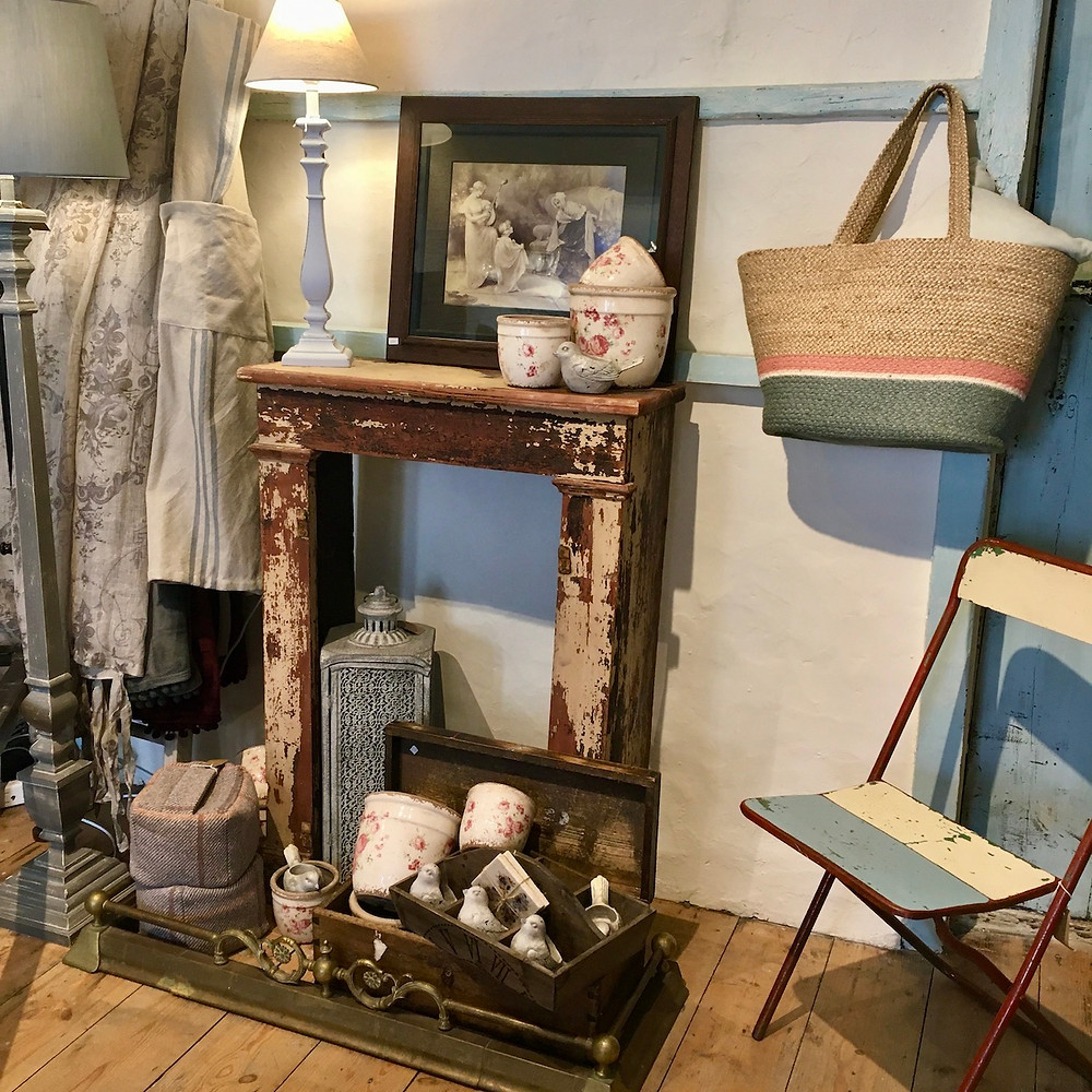 A wooden French fire surround with rustic shabby chic styled accessories at Source for the Goose