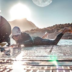 Triatleta a contraluz emergiendo del agua