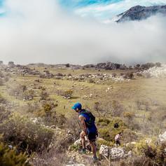 Corredor de trail con fondo de nubes