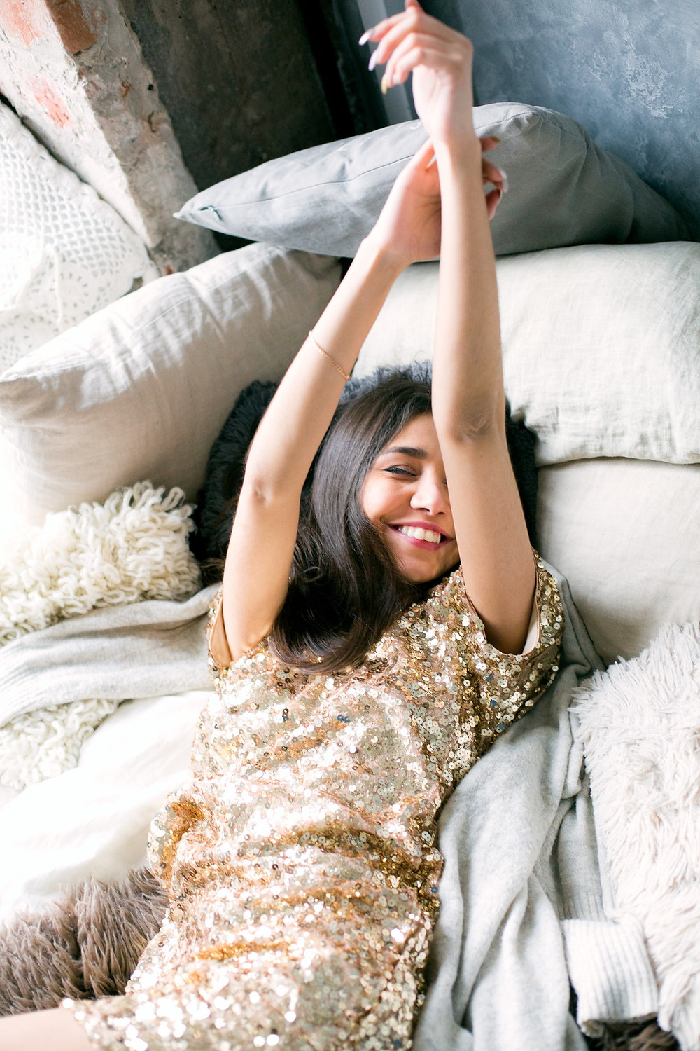 Woman in a Gold Sequin Dress on her bed smiling
