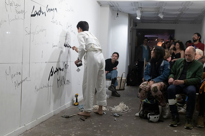 Artist Alexander Si installation view at Chinatown Soup, Lower East Side, New York, curated by Ventiko, with ropes, chains, celebrity names on wall