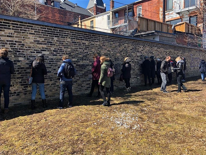 A line of people standing and touching the historic CAMH hospital wall built by patients.