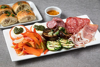 antipasti dish with grilled vegetables, prosciutto, salami, and caprese salad