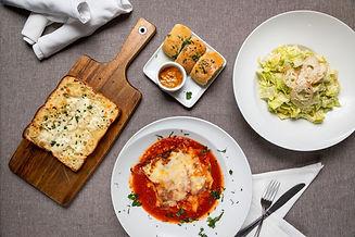 garlic bread with cheese, lasagna, and a Caesar salad