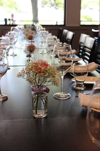 A set table with wine glasses, and beautiful flower vases as centrepieces