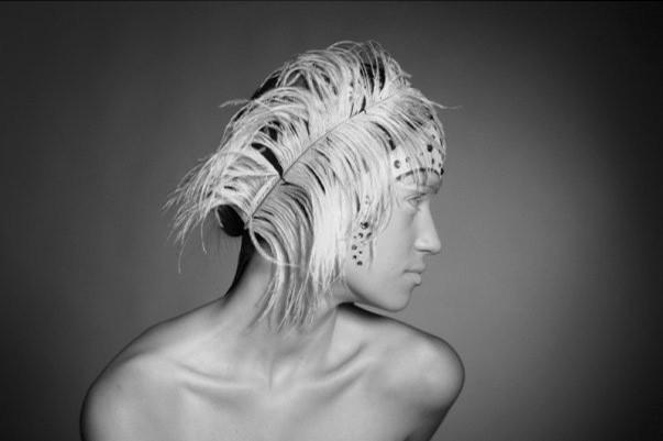 Mulher com pluma no cabelo a olhar para o lado