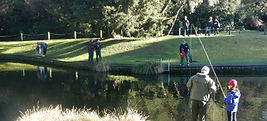 Volunteers and children fishing at pond