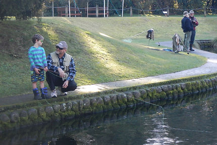 Volunteer and kid fishing at pond