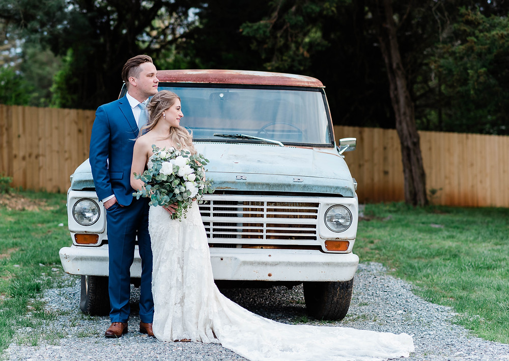 The bride and groom standing in front of a vintage truck at Persimmon Creek Barn