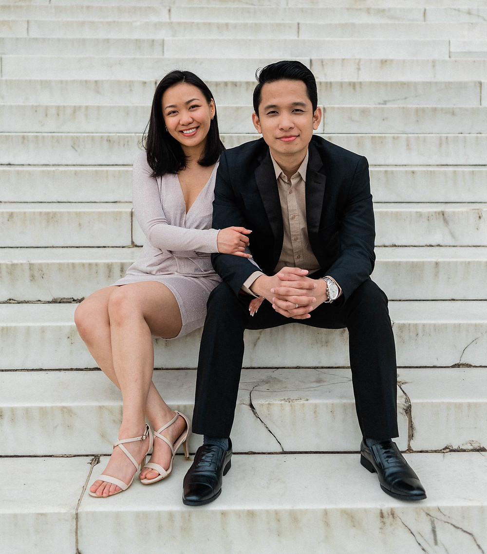 A portrait of the couple looking at the camera, sitting on the steps.