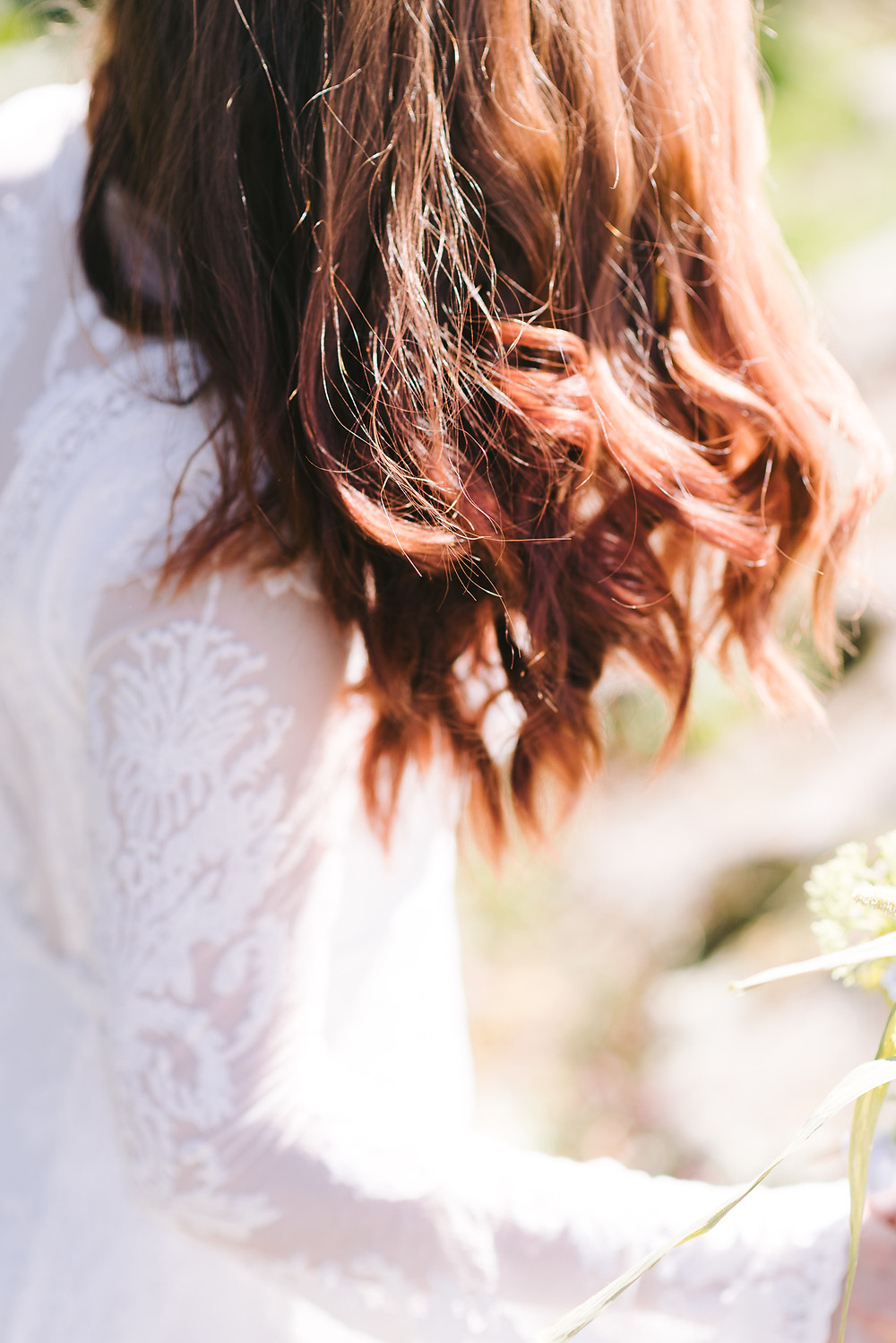 The bride's beautiful red hair glistening in the sun.