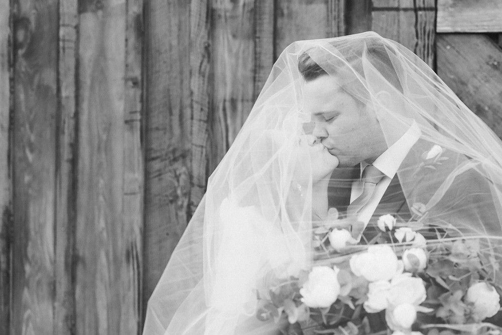 Black and white portrait of the bride and groom, under the bride's veil.