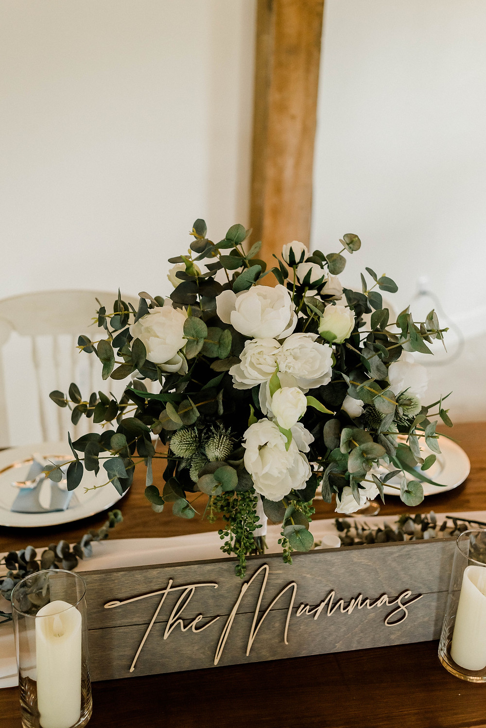 Details of the decor at the sweetheart table.   White wedding florals.