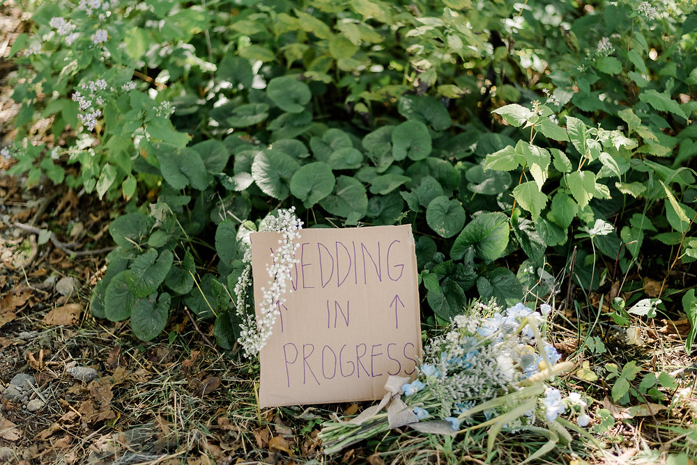 wedding in progress sign pictured amongst the greenery outside.