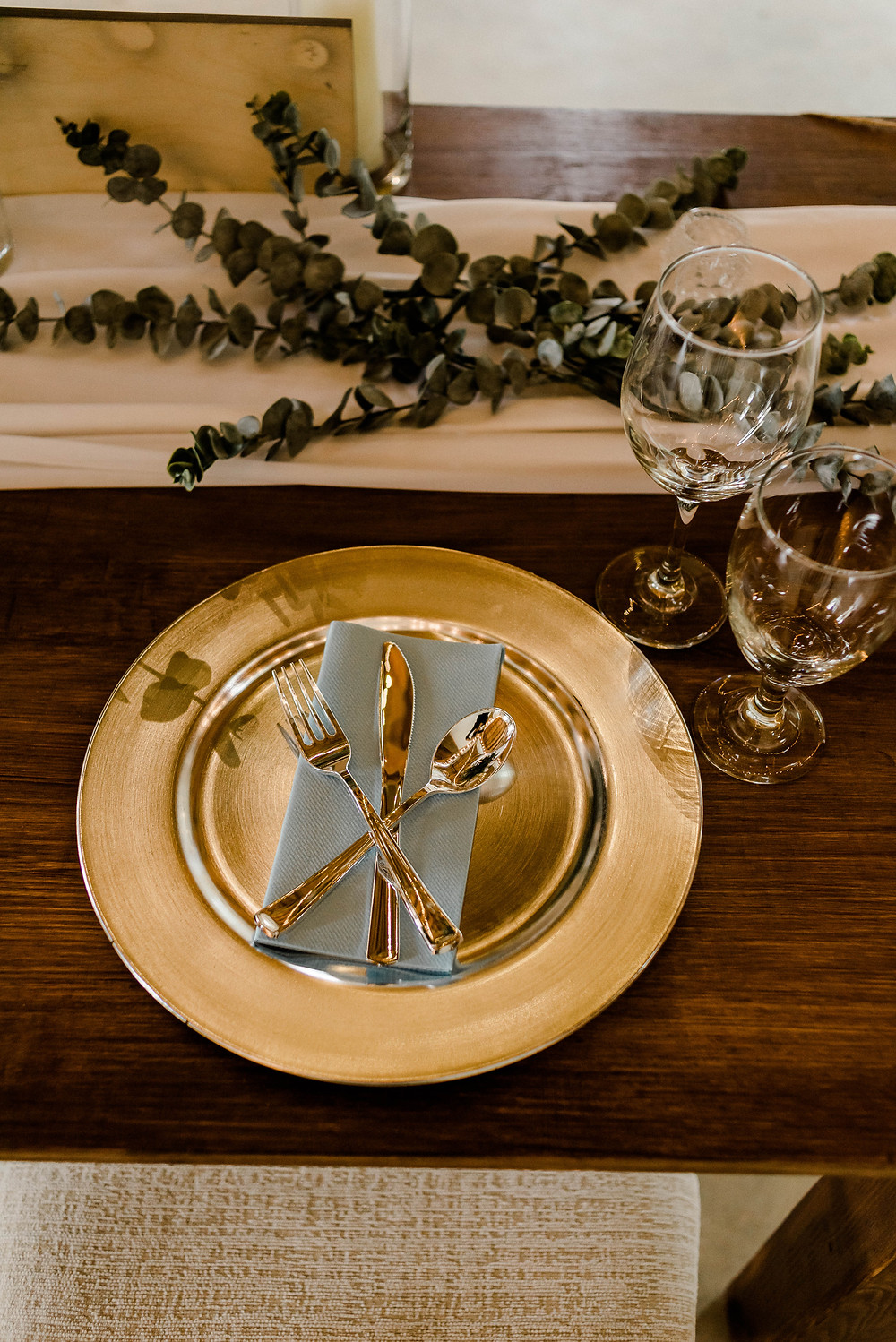 Gold and eucalyptus table setting at the sweetheart table.