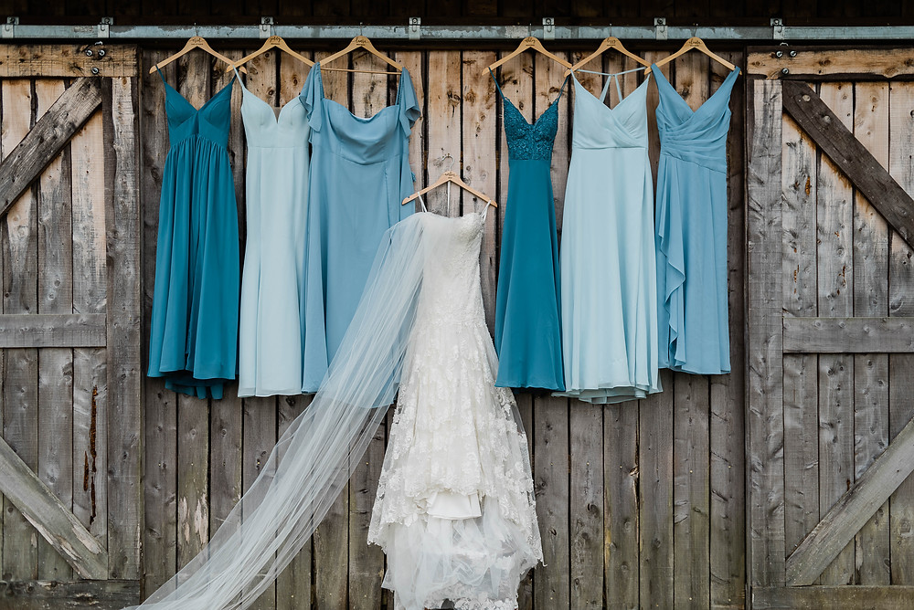 Portrait of the wedding gown between the bridesmaids' gowns