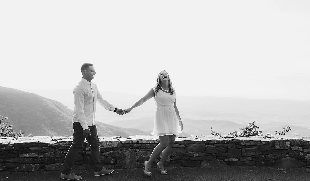 Black and white portrait of the couple with the overlook behind them.
