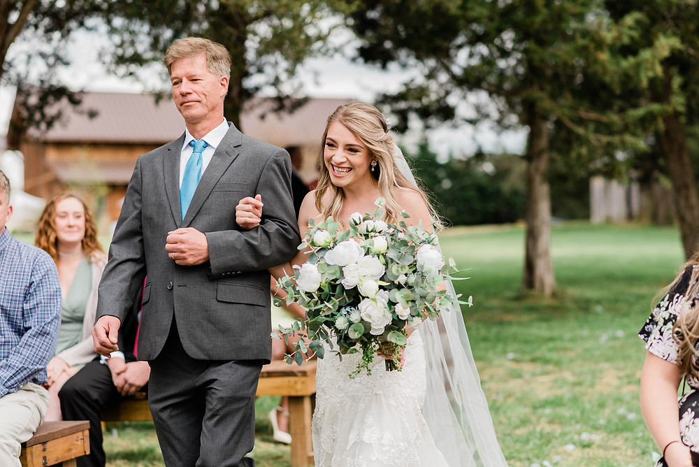 The bride being escorted down the aisle by her father.
