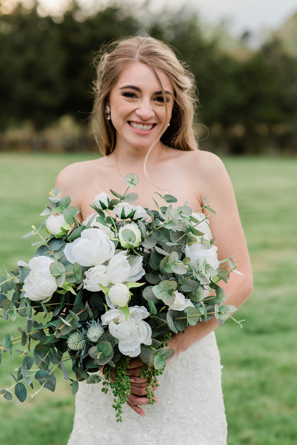 The bride smiling at the camera holding her bouquet.