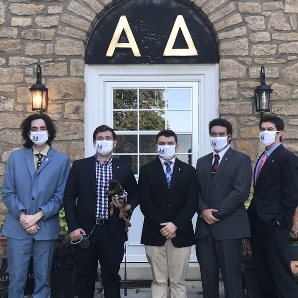 Brothers standing in front of the Alpha Delta house.