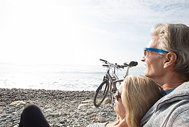 retired couple on beach with bicycles admiring the view and discussing private medical insurance