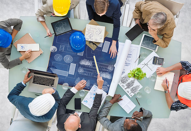 employees discussing construction design on desk