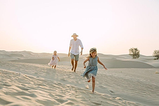 Father and daughters running on sand dunes