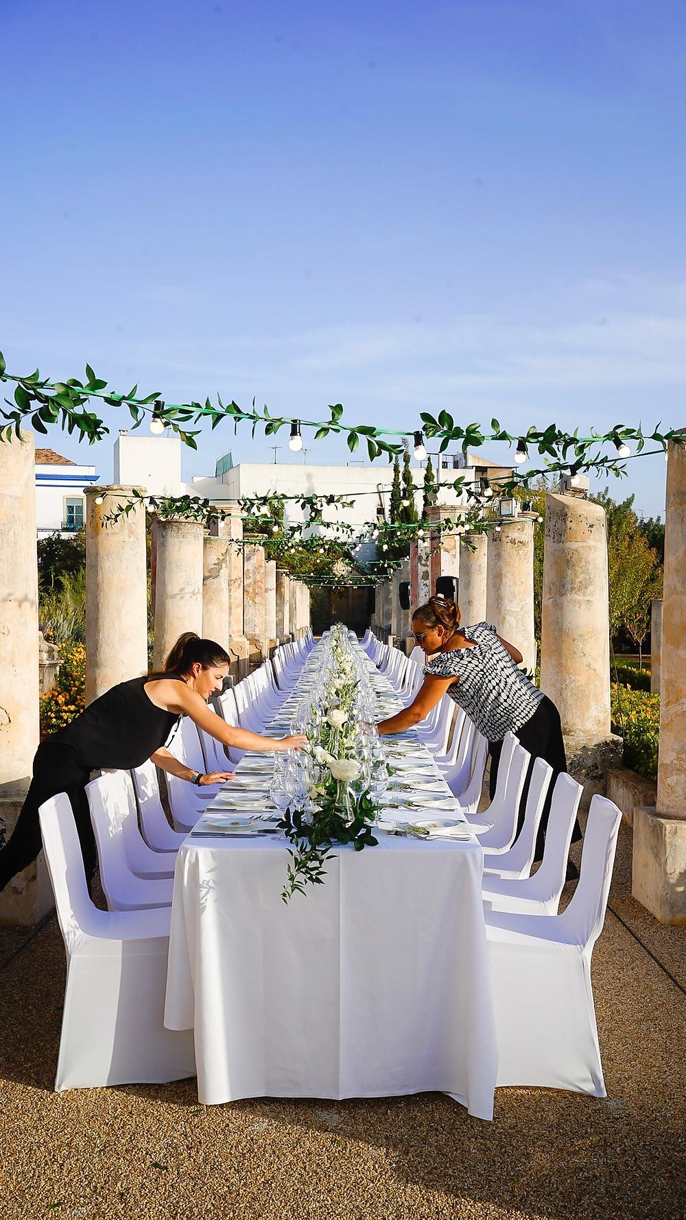 Wedding Planners decorating dinner table at Pousada de Estoi Wedding Venue Faro Algarve Portugal
