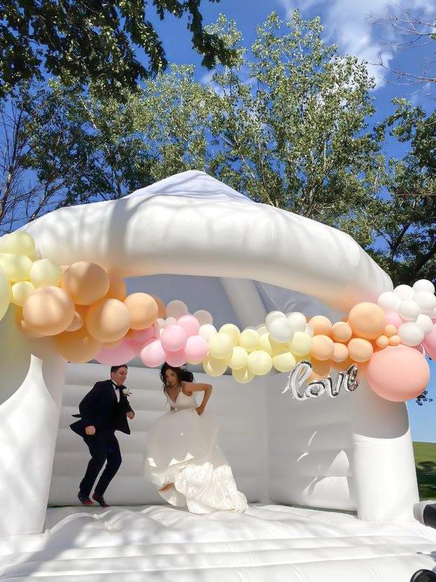 Château gonflable blanc avec guirlande de ballons