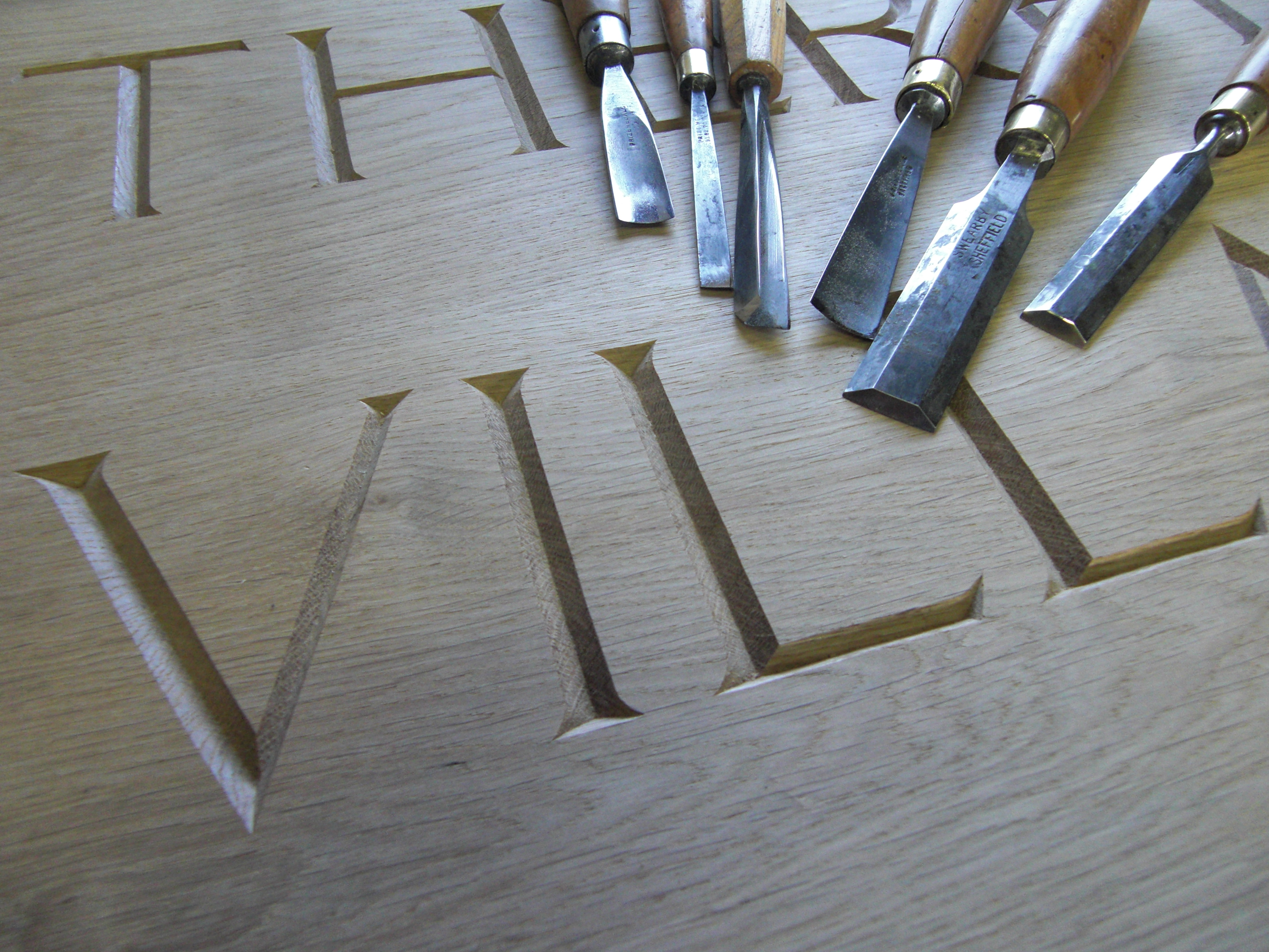 Craved lettering with chisels. board made of oak