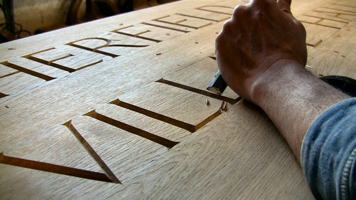 Carved lettering on oak board