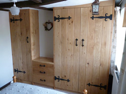 Built in oak bedroom furniture, with wrought iron hinges and handles