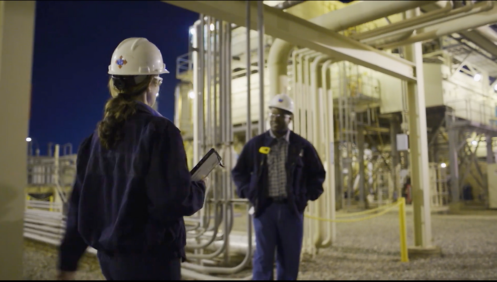 Two energy workers in hard hats at a natural gas facility